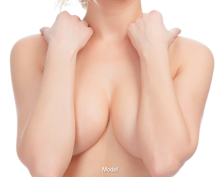 A beautiful woman covering her breasts with her forearms.