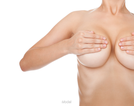 A woman covering her two large breasts with her hands.