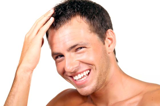 Man smiling and laughing while running his fingers through his hair