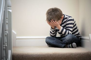 A young child sits on top of the stairs with his head in his hands