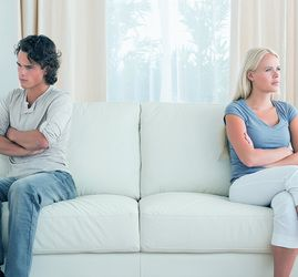 A couple sits angrily on opposite ends of a couch not looking at each other