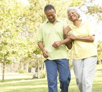 Elderly African American Couple Walking Through A Park In Hopes of Losing Weight