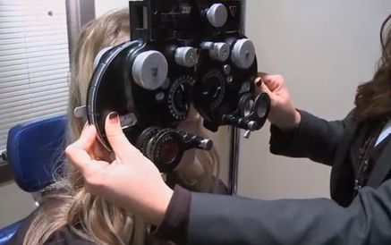 A patient looking through a vision acuity device