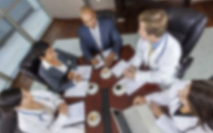 A blurred image of a business meeting with administrators and doctors