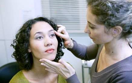 A young woman being examined by a cosmetic consultant