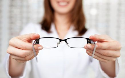 An optician holding a pair of eyeglasses in the foreground