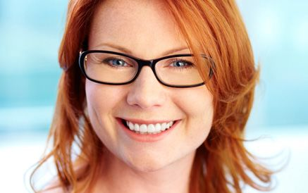 A young woman with glasses and red hair
