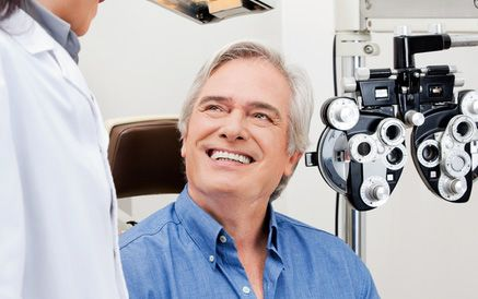 A middle-aged man sitting in the eye exam room with a doctor
