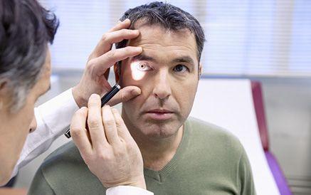 A man undergoing an eye exam has a light shone in his eye