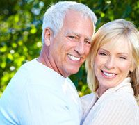 An older couple hugs and smiles together after receiving dental implants