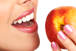 Woman with dental implants from Tischler Dental in New York eating an apple