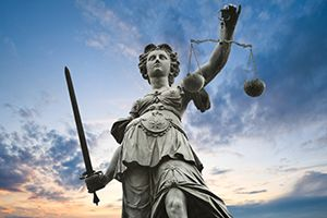 Justice statue with sword and scales against sunset