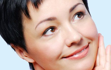 Woman with short hair grinning while stroking her face