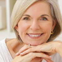 An older woman smiles confidently after seeing a TMJ specialist