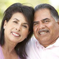 An older couple smile together after undergoing a smile makeover