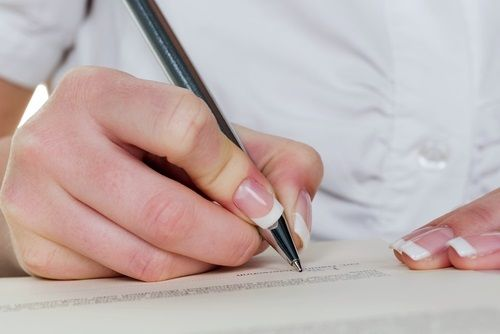 photo of a hand filling out paperwork
