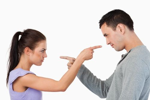 Photo of a man and woman pointing at each other