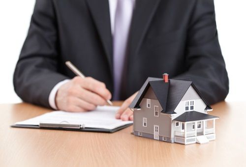 Photo of man in suit with paperwork and a house model on a desk