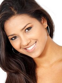 Brunette woman smiling following a tooth extraction