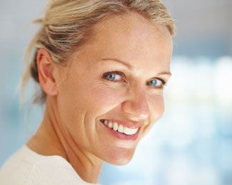 Woman with blue eyes wearing her hair up and smiling