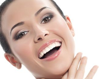 Brunette female smiling while stroking her chin