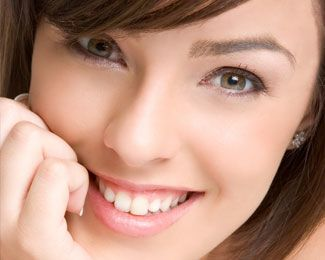 A close up of a young brunette female smiling