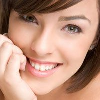 Brunette female smiling while resting her chin on her hand