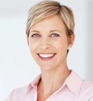 middle aged woman with short hair and blue eyes smiling
