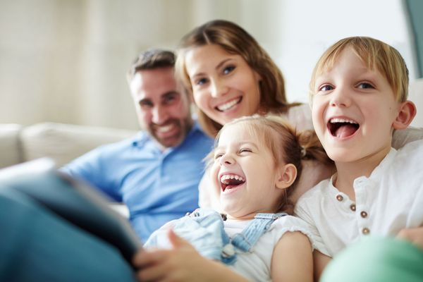 Family Dentistry: a closeup on a family of four, laughing into the camera