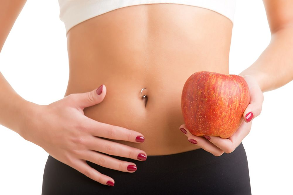 A woman shows off her stomach while holding an apple