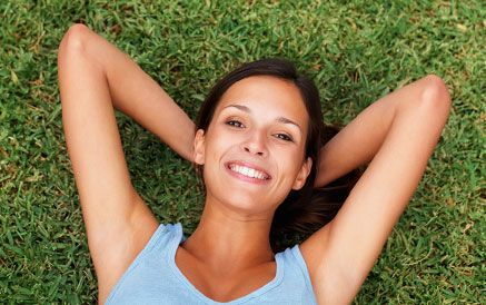 Woman lying on the grass, pleased with her good health