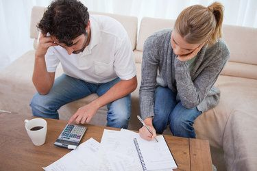 couple looking at documents with calculator