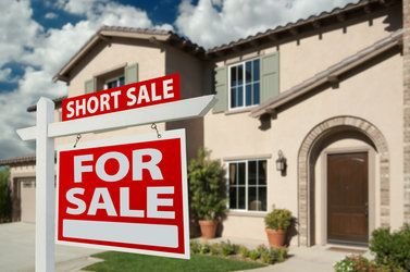 Short sale sign in front of house