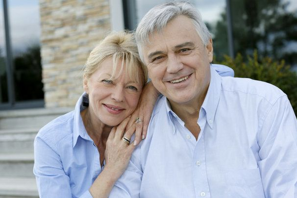 older couple looking happy in front of home