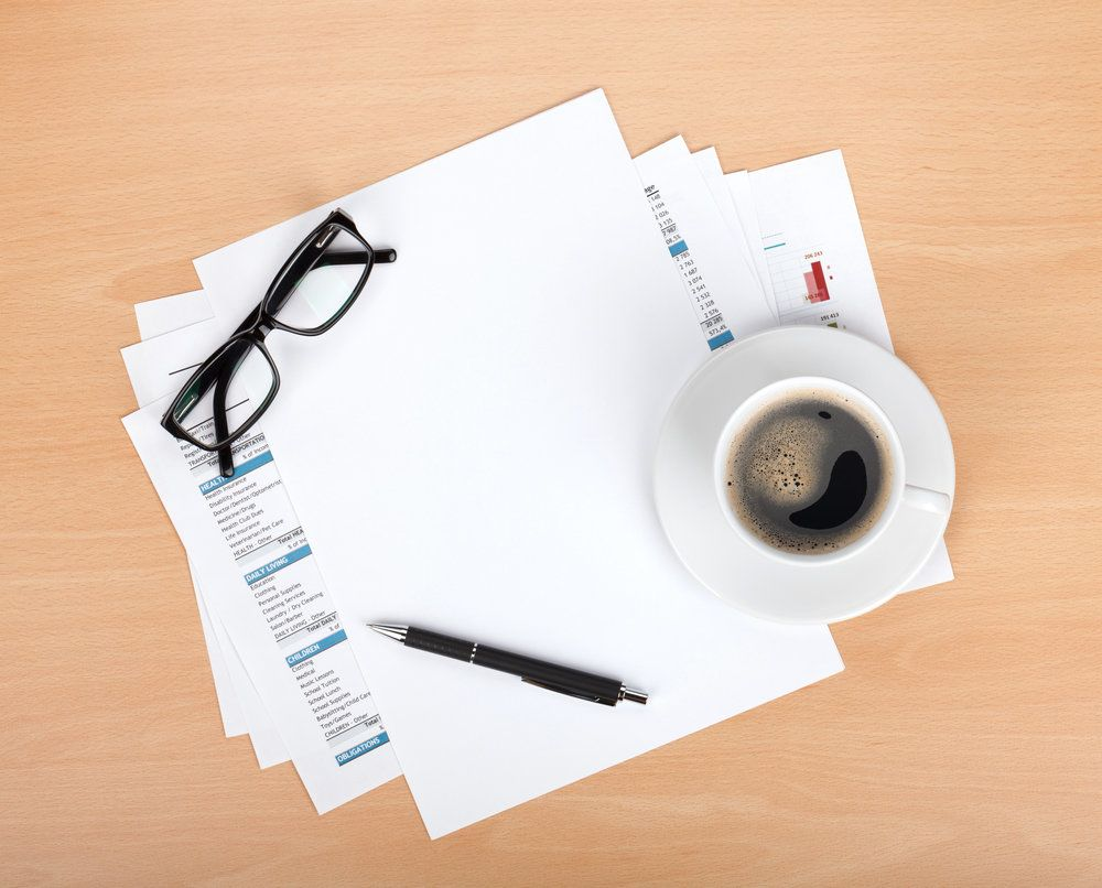 Papers on a desk, under a cup of coffee and pair of glasses