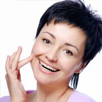 a short-haired woman places her finger on her cheek to show off her smile