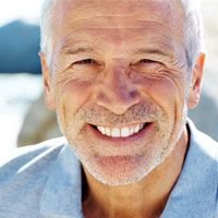 An older man smiles after having a full-mouth reconstruction