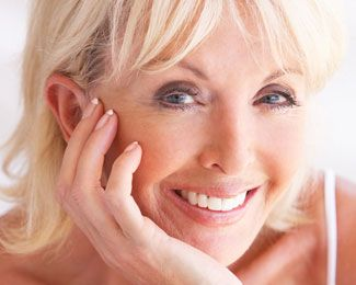 a blonde woman smiles to show off her new dental crowns