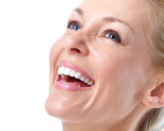 a blonde woman laughs gleefully after having her cavities filled