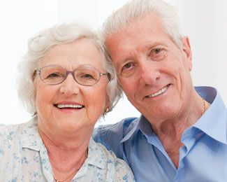 an older couple with dentures smiles together