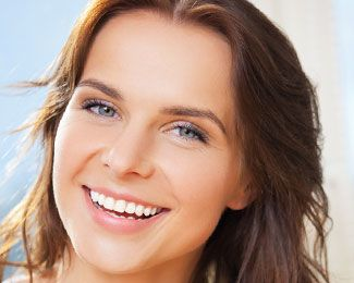 a young brunette woman woman smiles to show off her porcelain veneers