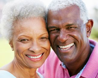 A couple smiles together after having dental implant surgery