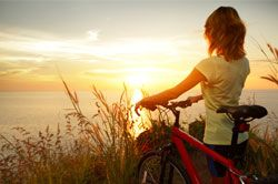 Woman standing with her bike looking out into the sunset