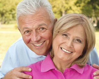 Smiling older couple with heads together