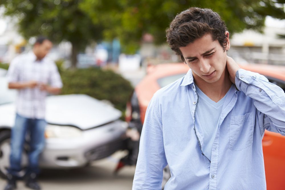 Photo of a man holding his neck by an auto accident