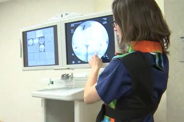 Image of woman explaining the readout on a monitor at the infertility clinic.