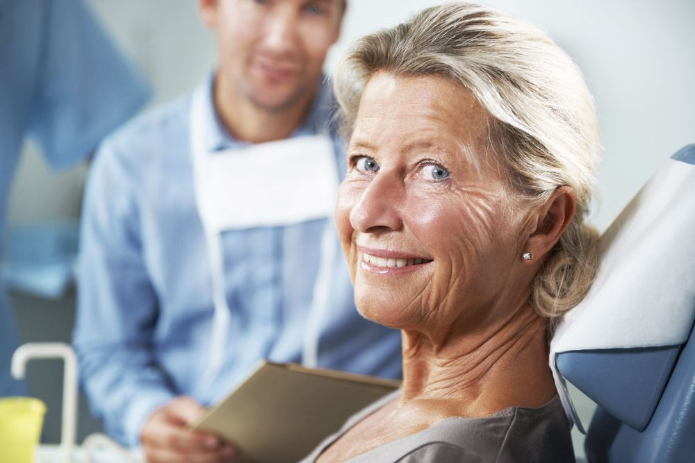 An older woman smiles in the dental chair after full mouth reconstruction
