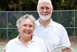 Elderly couple smiling and pausing during a tennis game