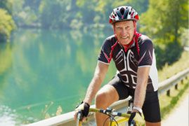 Elderly man in bicycle gear riding near a picturesque lake