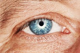 Close up of elderly man's bright blue eye.